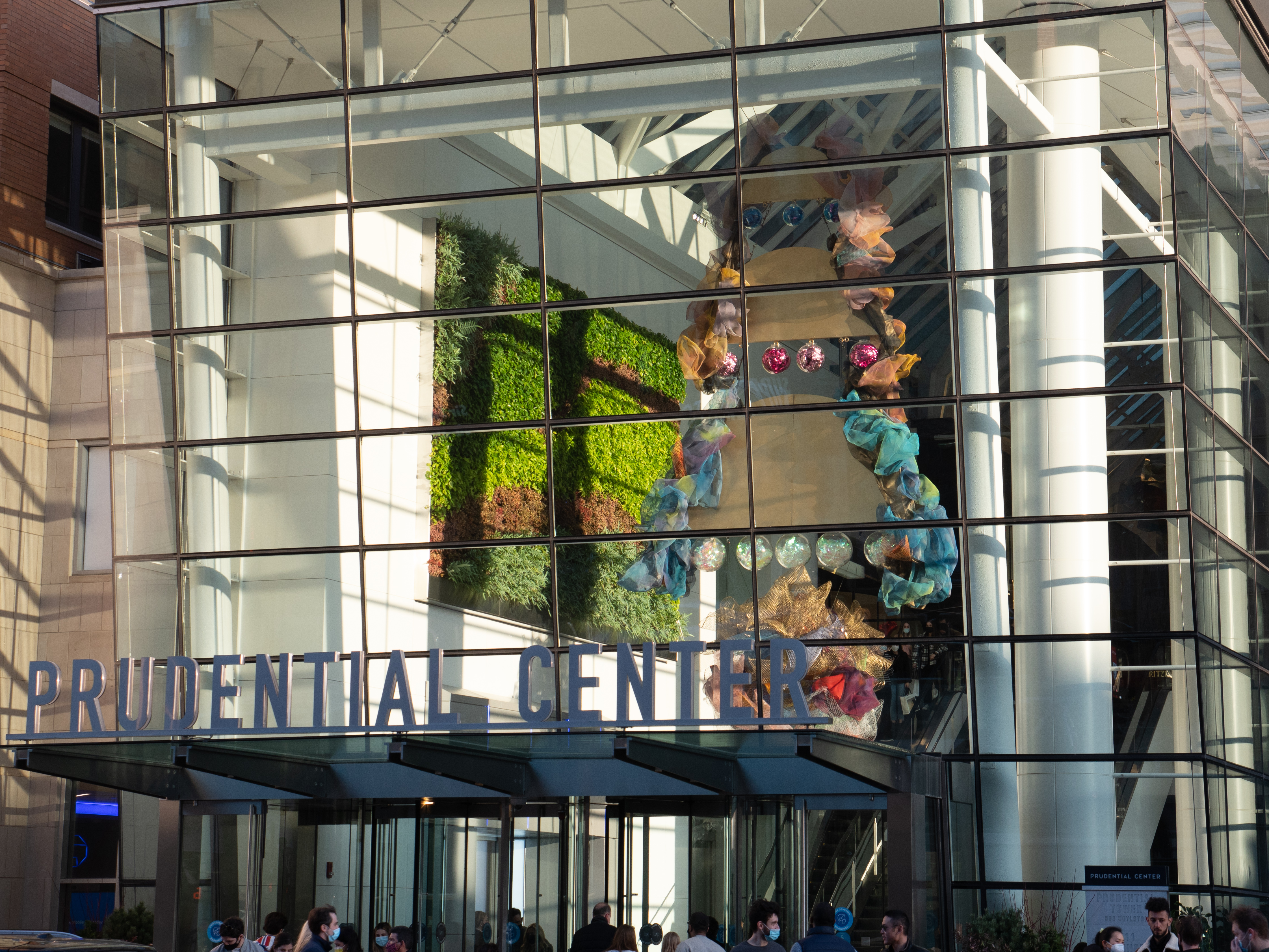 """Three half circles with a border of mesh hanging one on top of the other with blue, pink, and translucent mirror balls. A mesh ball hangs below the half circles. The sculpture can be seen through a glass wall behind the """"Prudential Center"""" sign."""