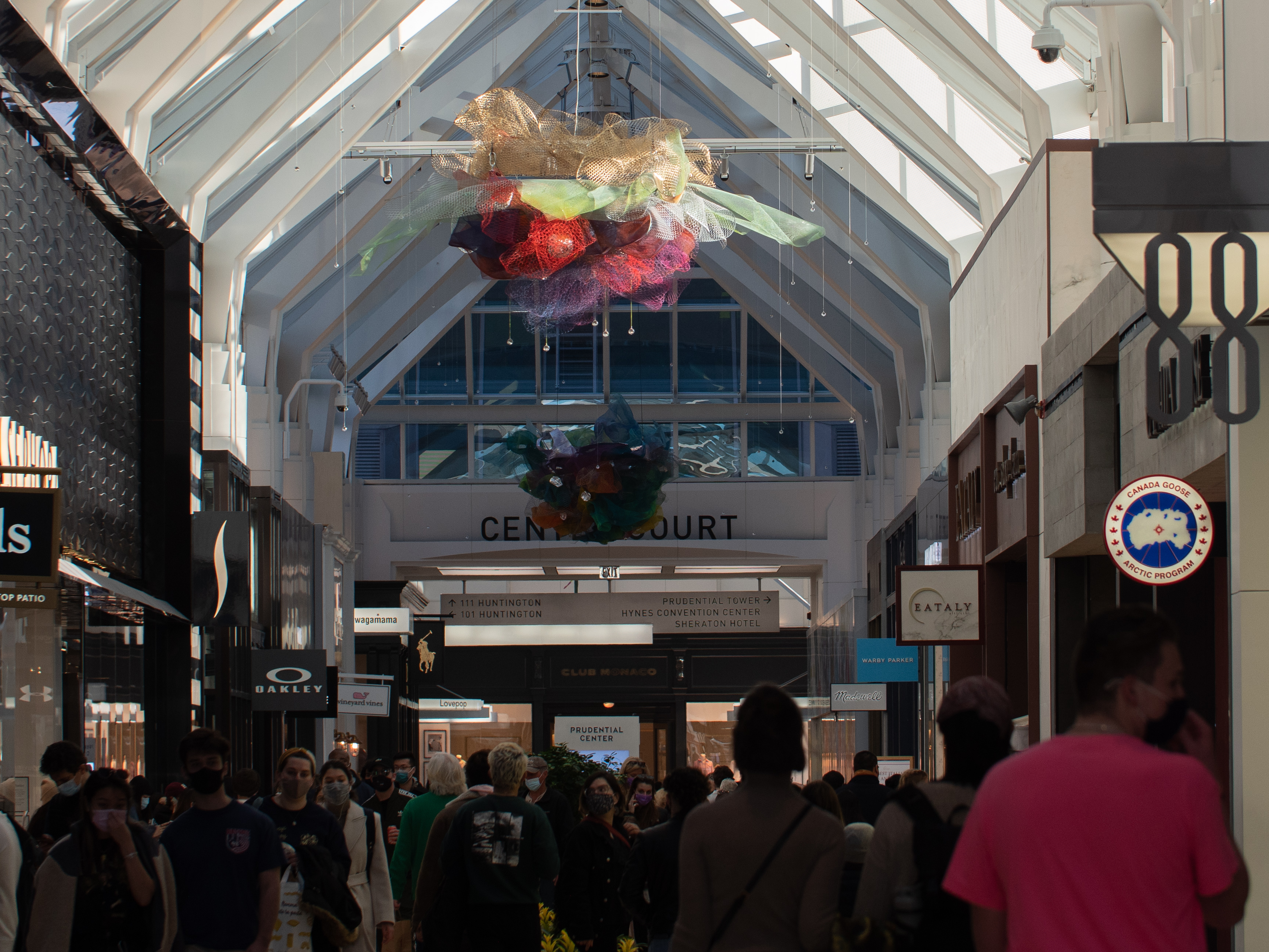 A mesh ball of beige, green, red, purple and a smaller mesh ball beneath of blue, purple, orange, green, and yellow hangs above shoppers and stores in the Prudential Center mall.