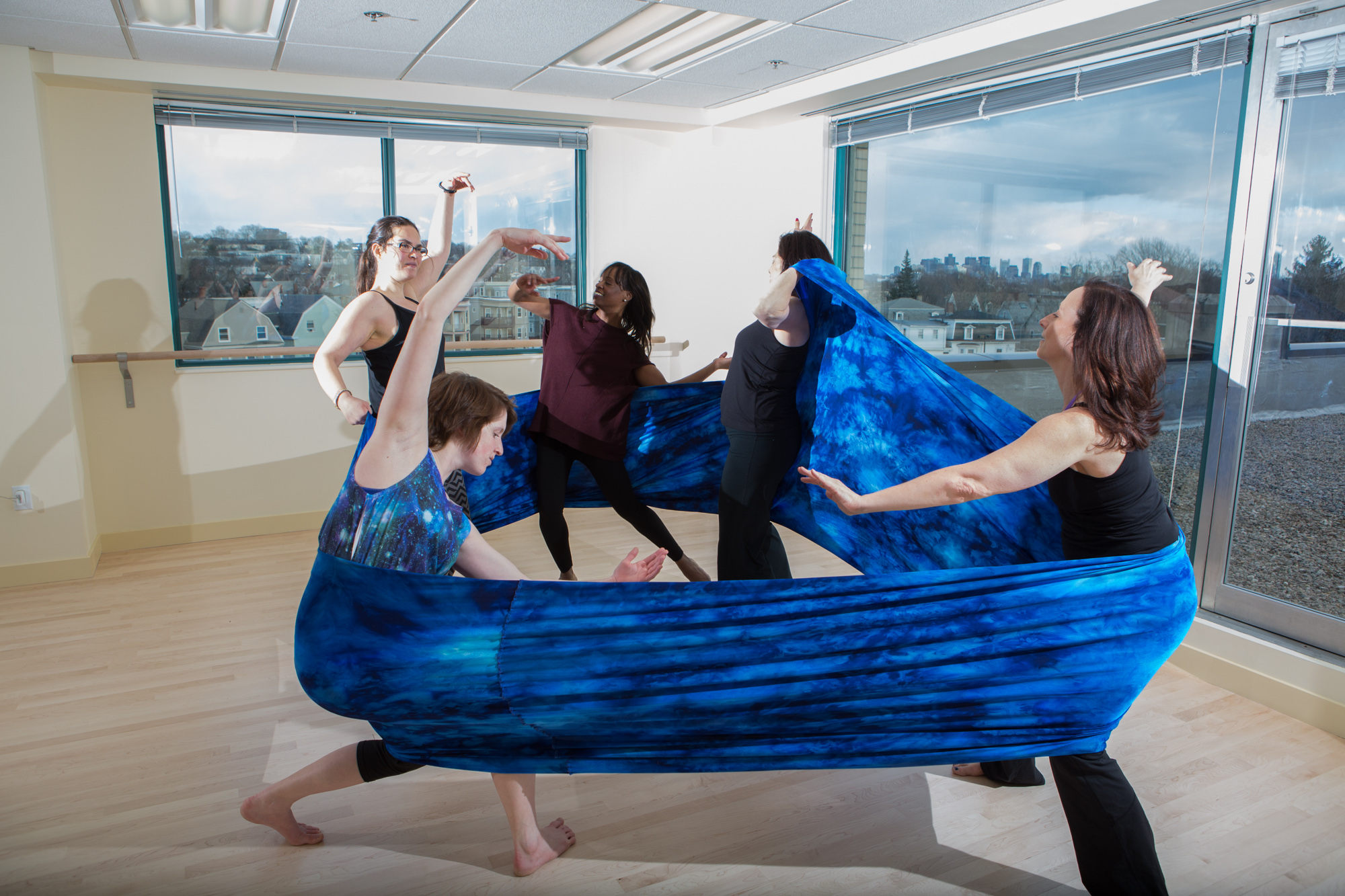 Dancers as part of a movement therapy class in a studio dancing with fabric.