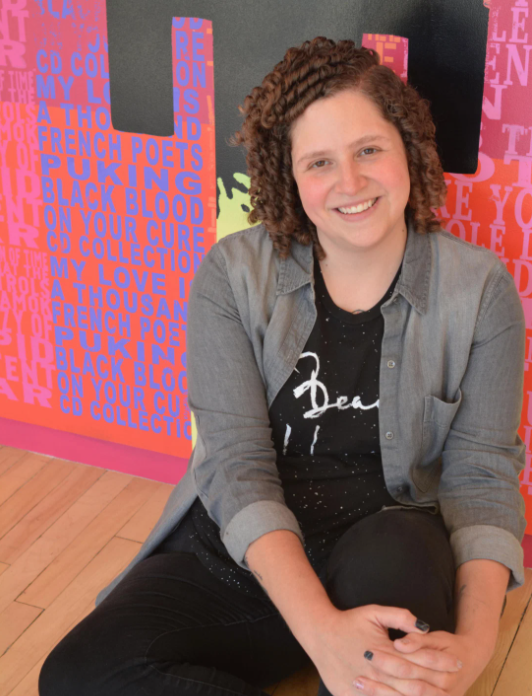Denise Markonish sits smiling in front of a bright red wall covered in letters. She has short curly brown hair and wears a jean jacket over a black shirt.