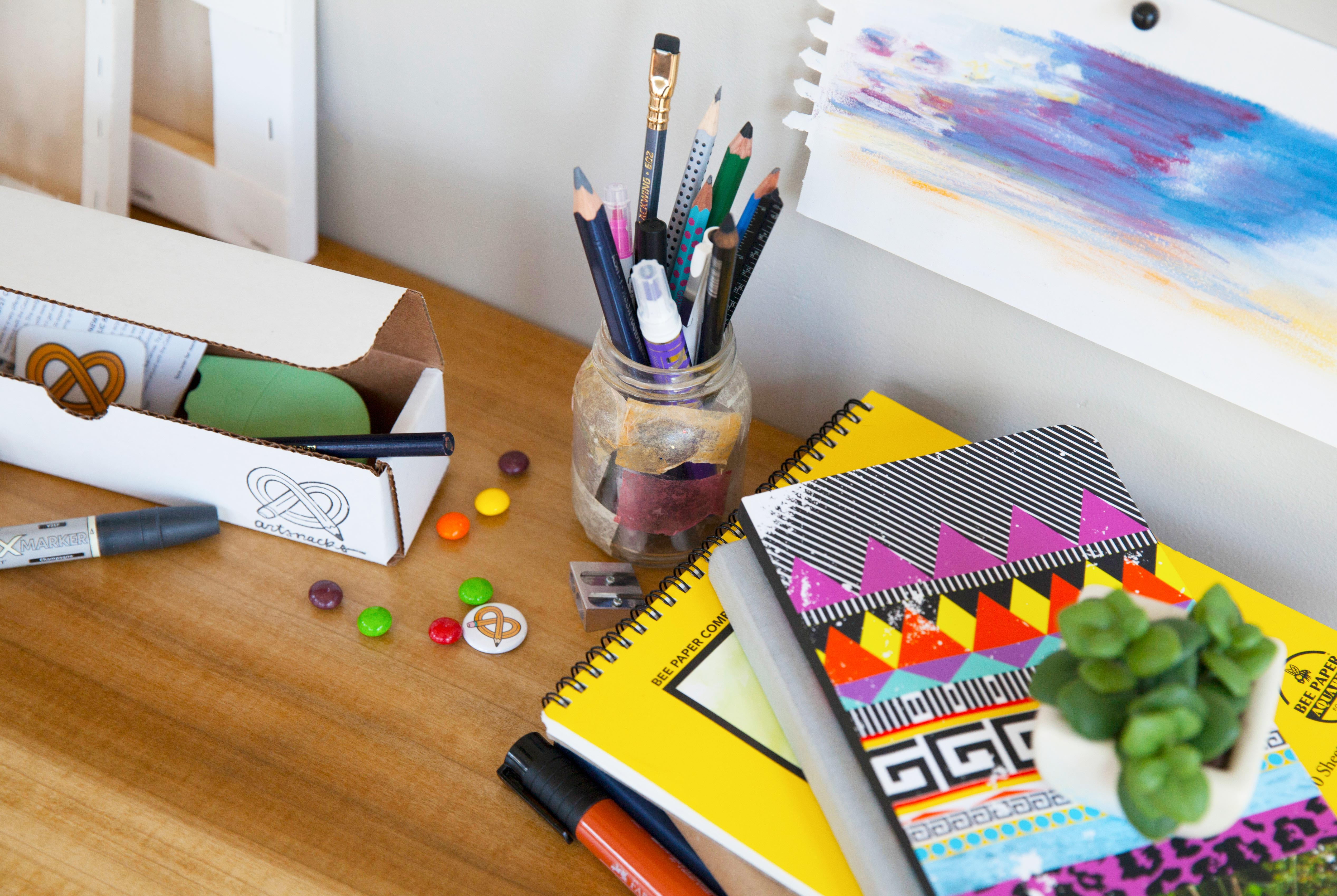 an open box from ArtSnacks sits on a desk next to books and paper