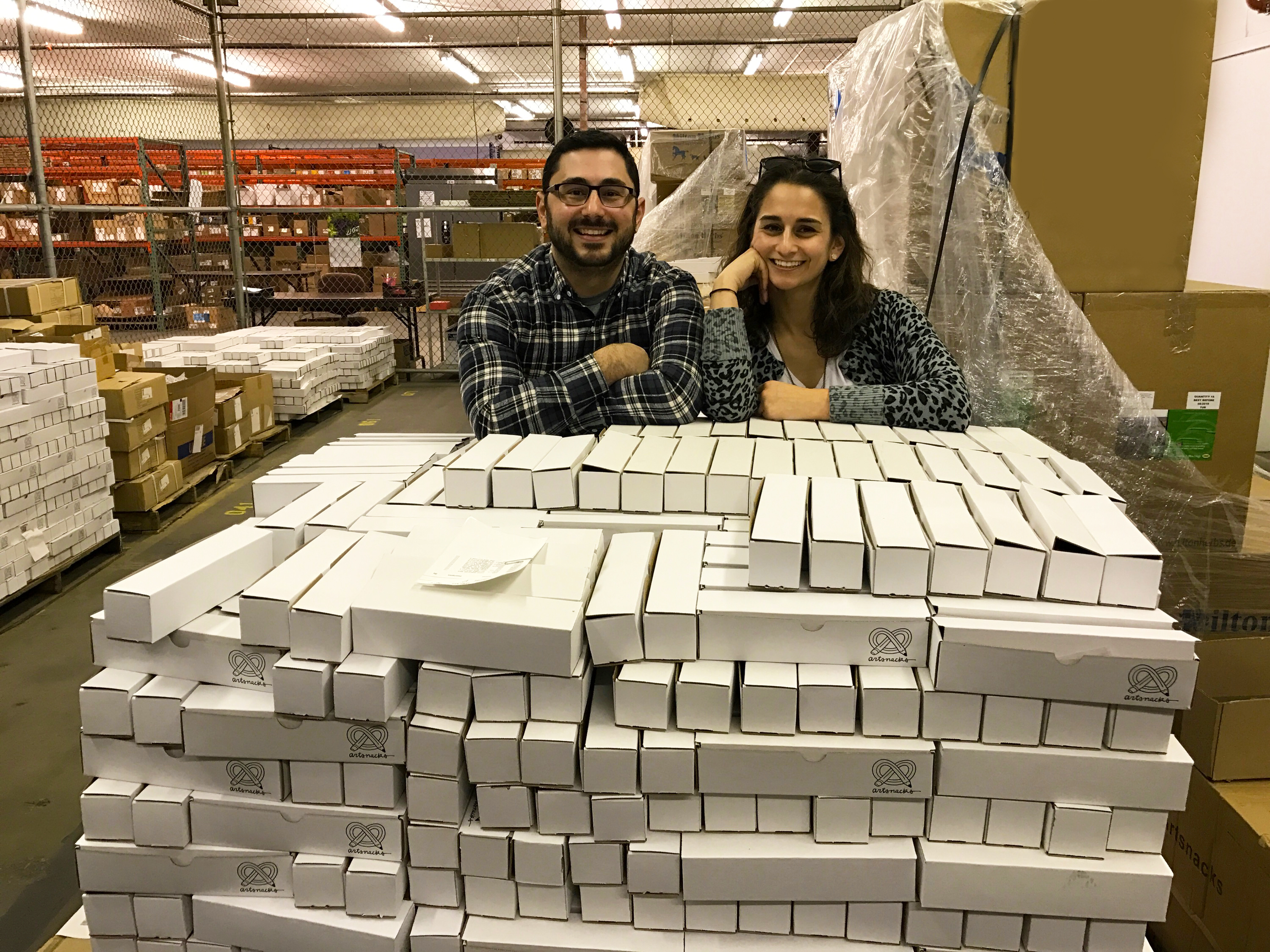 Sarah and Lee pose next to a large shipping pallet of ArtSnacks boxes.