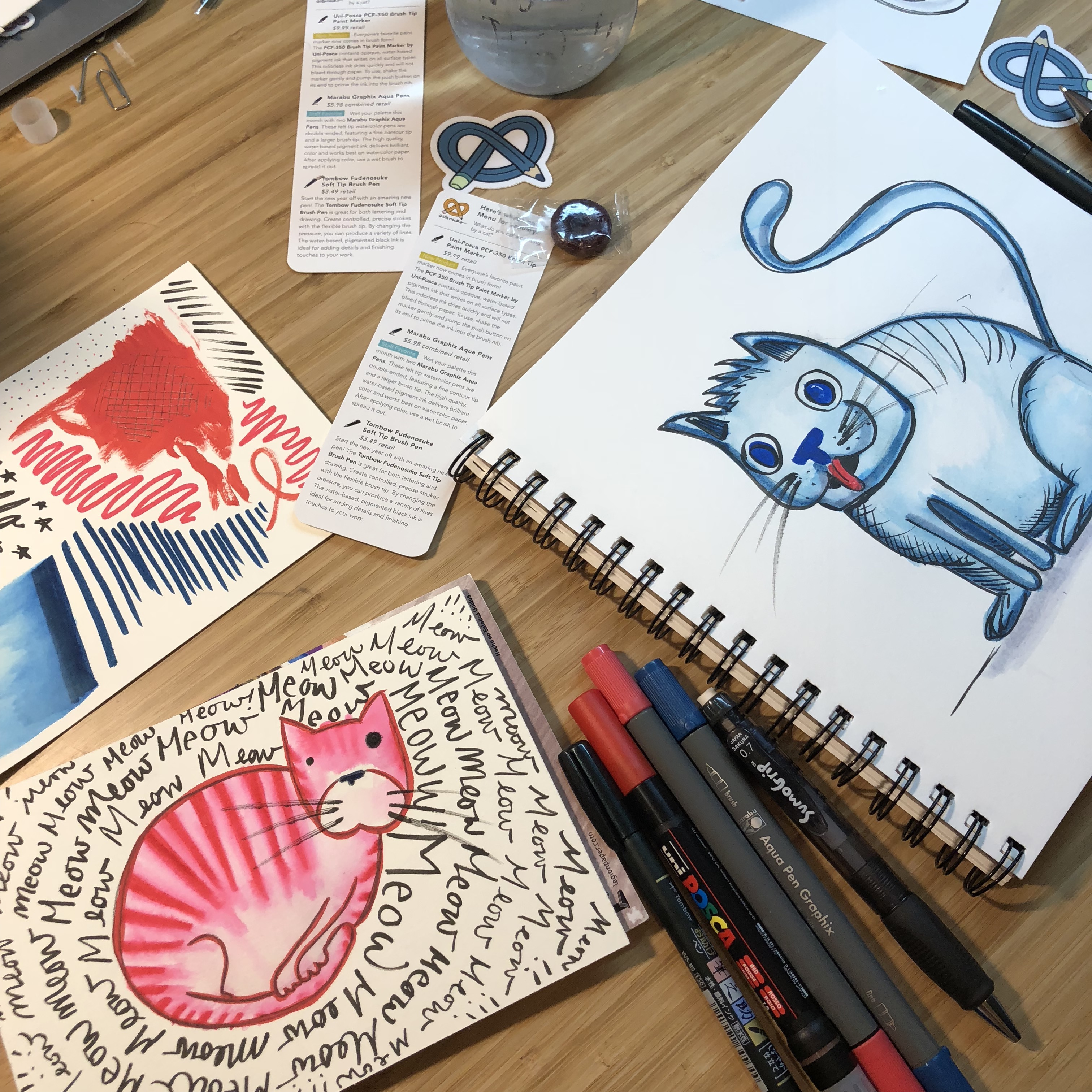two pads of drawing paper with illustrated cats sit on a table surrounded by pens