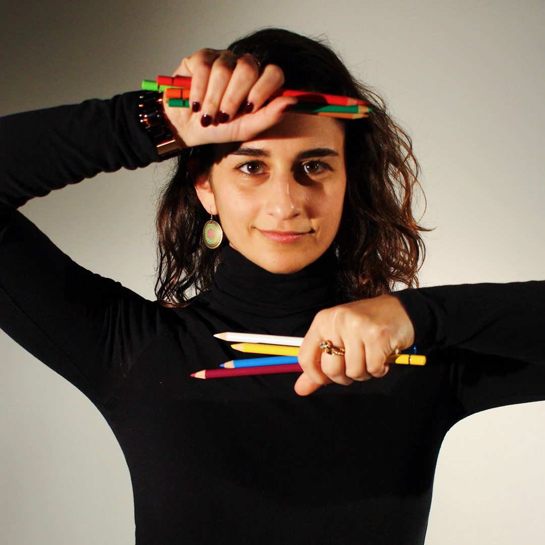 Headshot of Sarah Rubenstein in a black turtleneck holding pencils