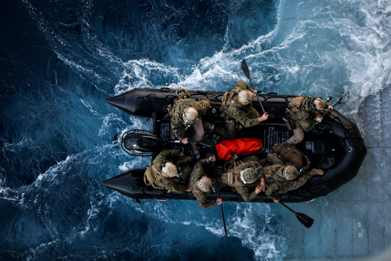 Overhead photo of troops in an amphibious vehicle on the sea.