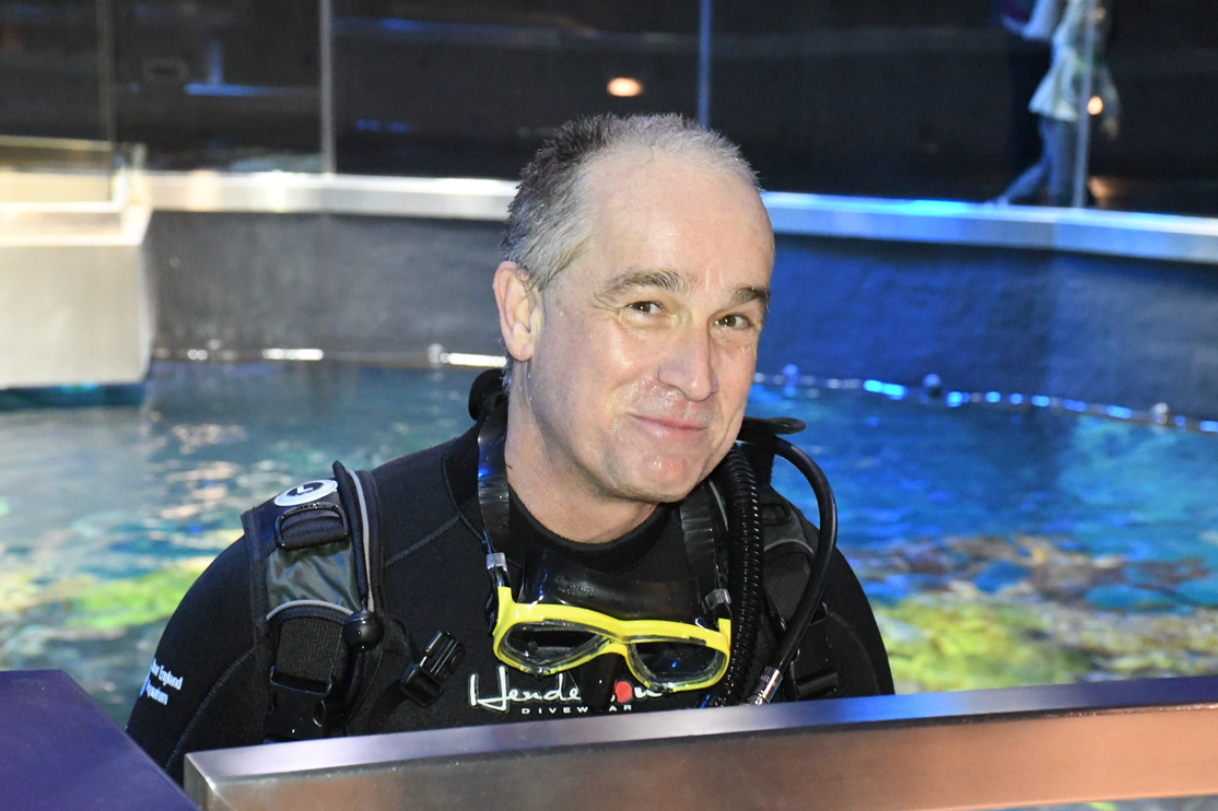 Threshold director Ernst VanBergeijk dives in the ocean tank at the New England Aquarium.
