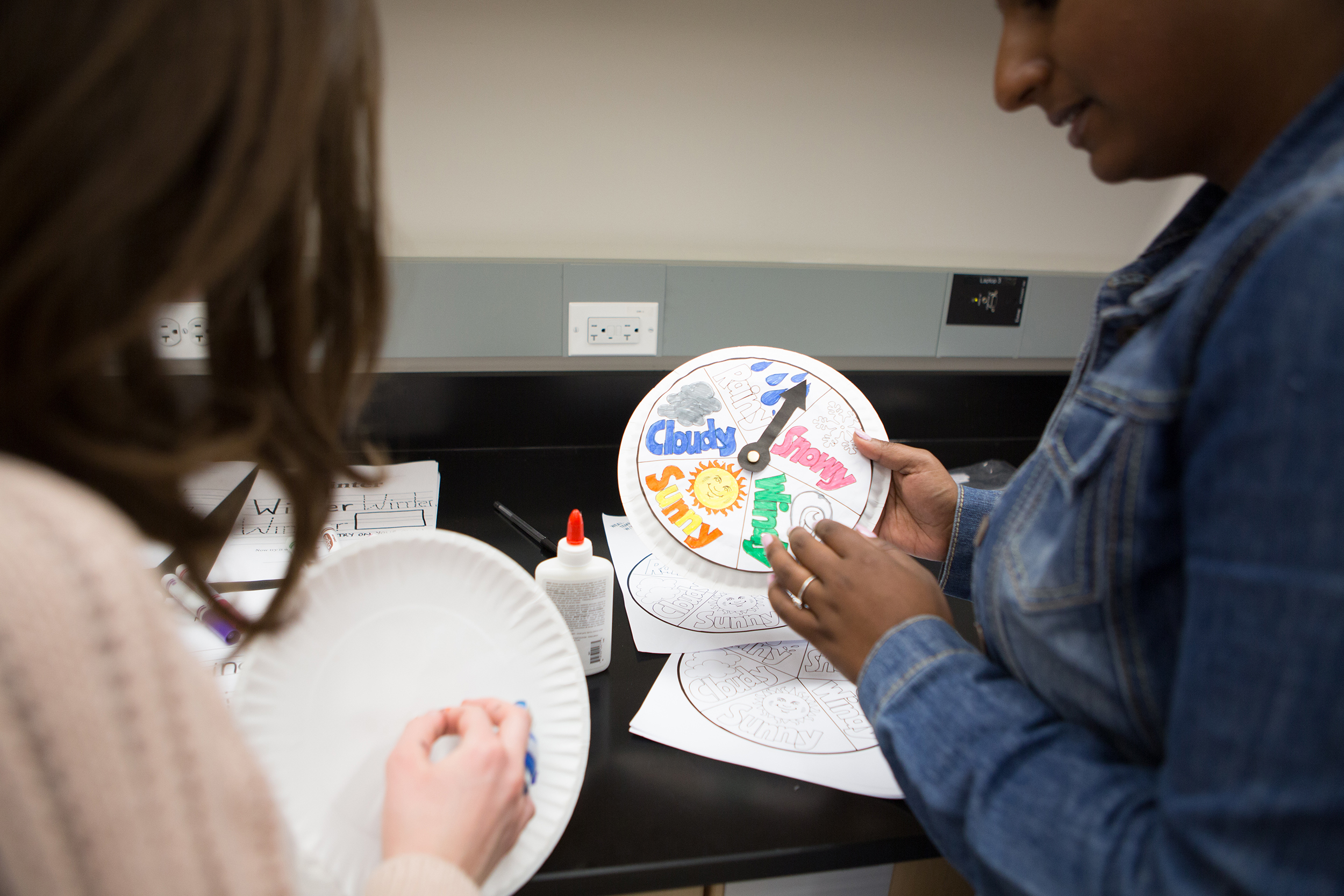 Lesley student holding a weather chart created on paper plate