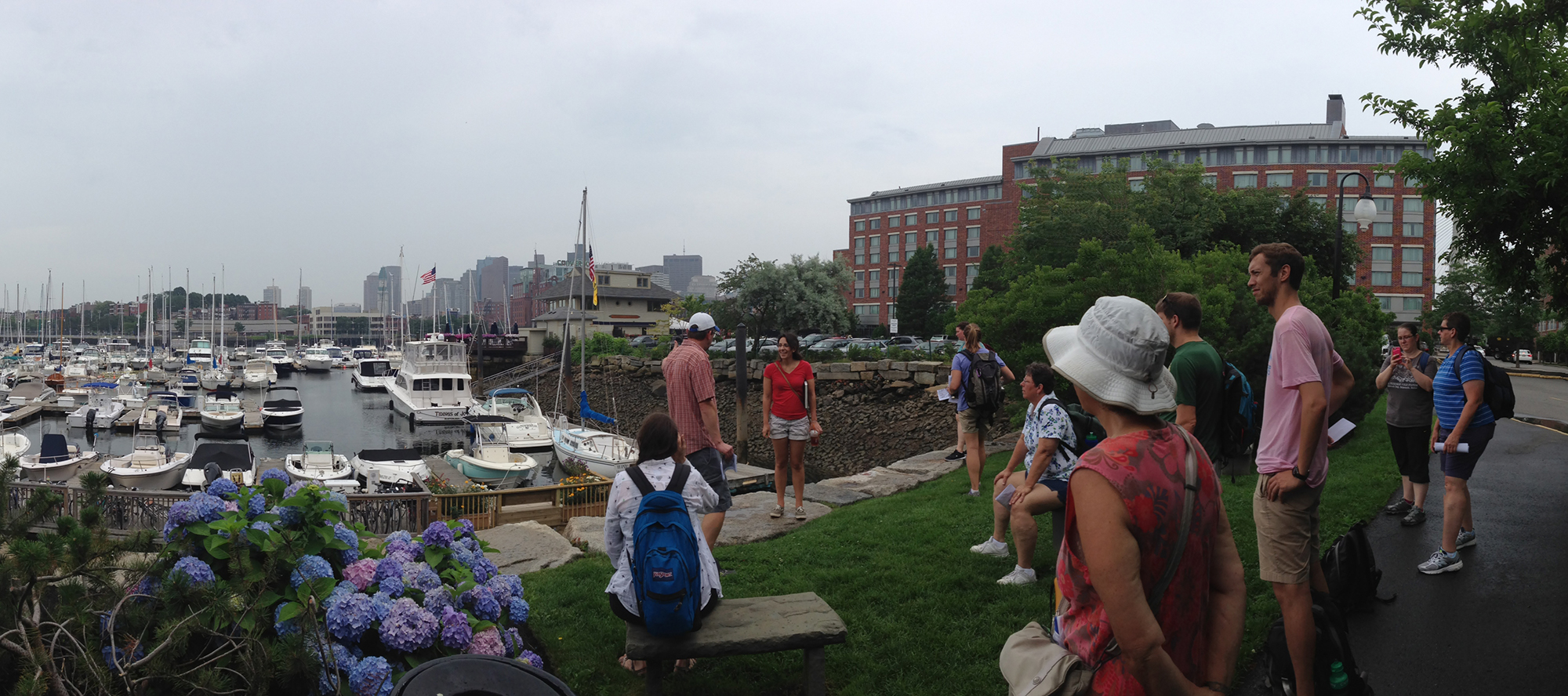 Students gathered at Boston Harbor, with skyline, sailboats, and greenspace