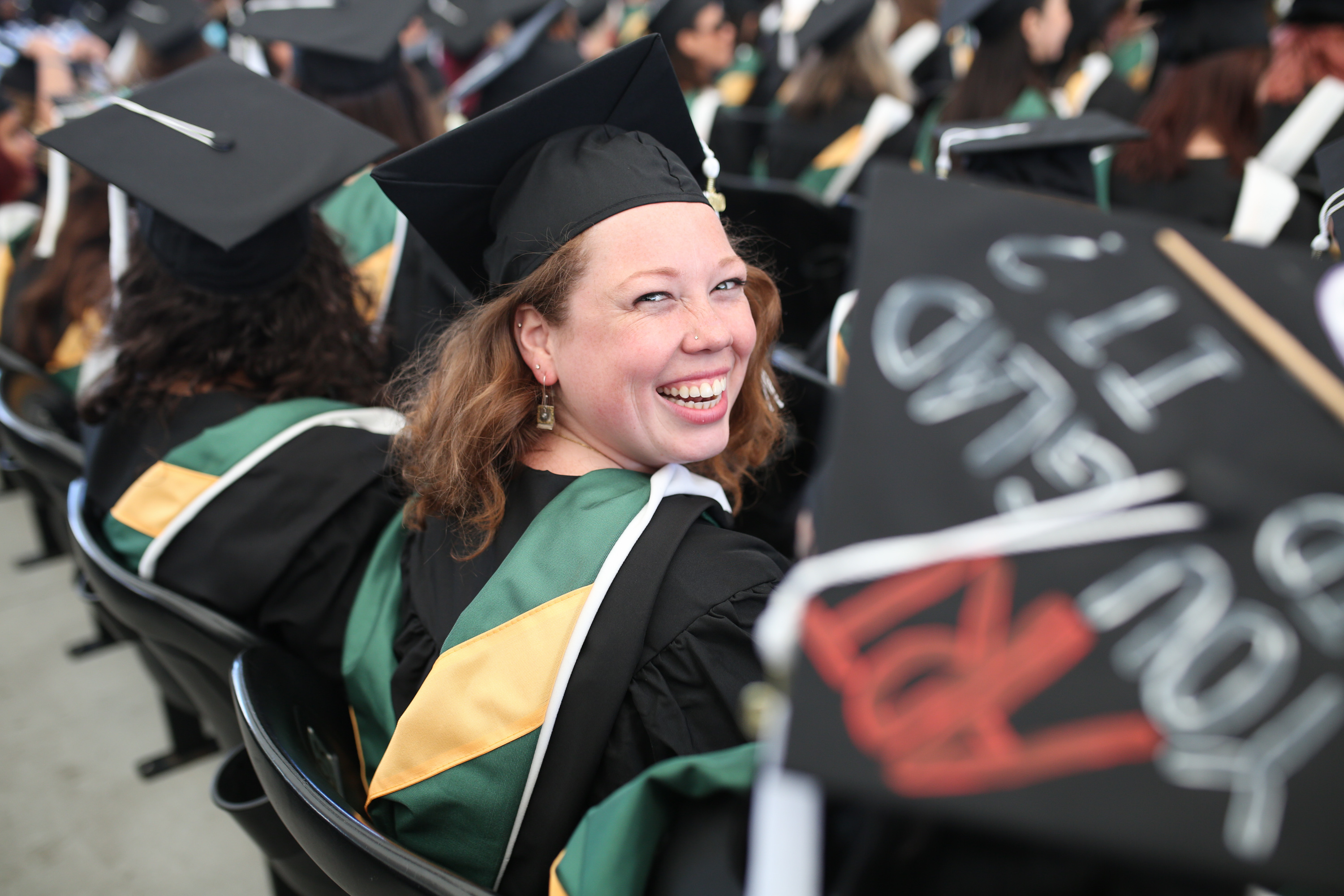 Female graduate looking back over her shoulder and smiling in the aisle.