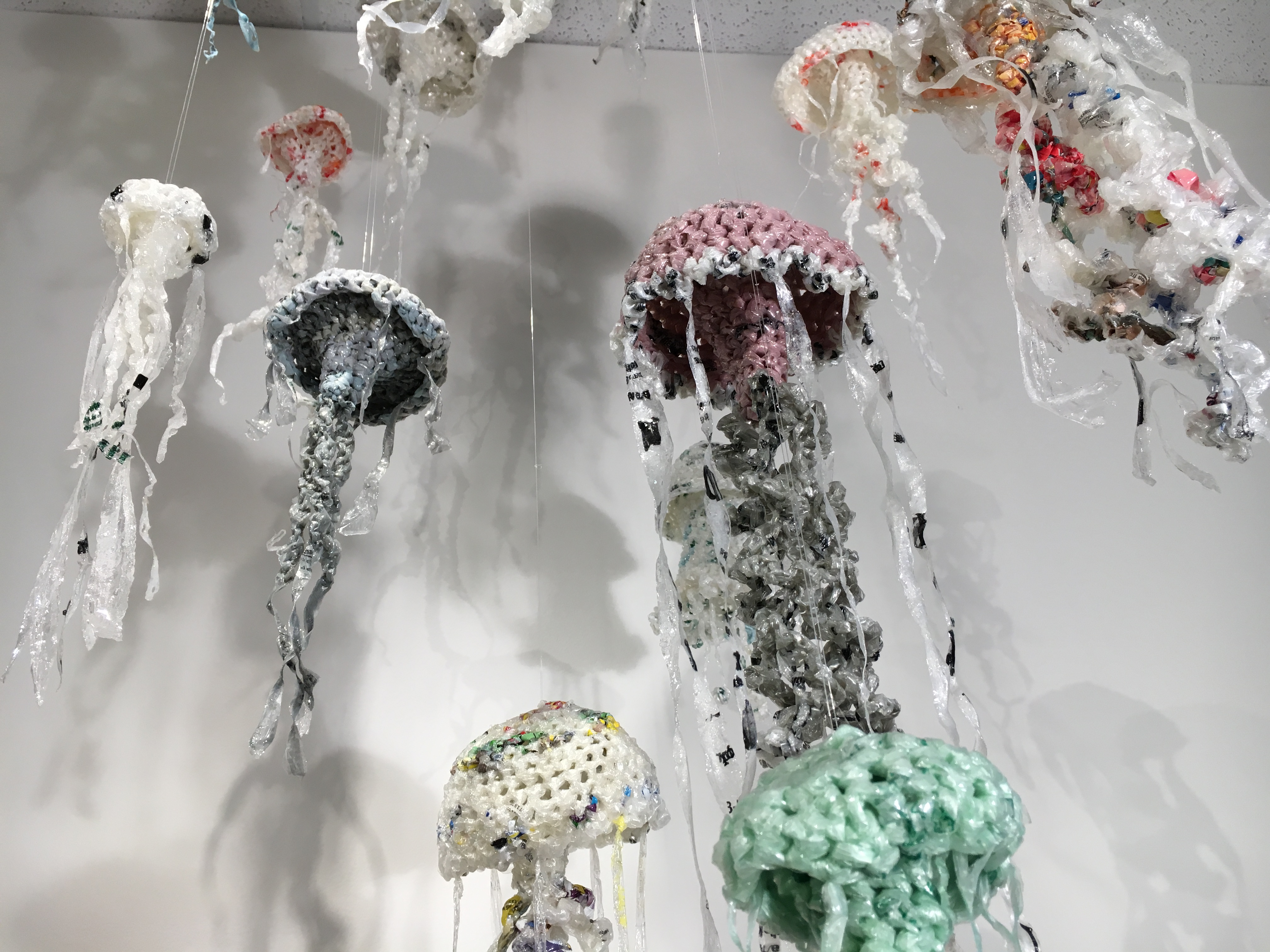 Jellyfish sculptures made of plastic hang from a ceiling