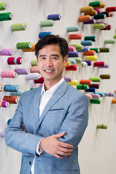 Lee Mingwei stands smiling with his arms crossed in front of spools of thread. Lee is wearing a blue suit.