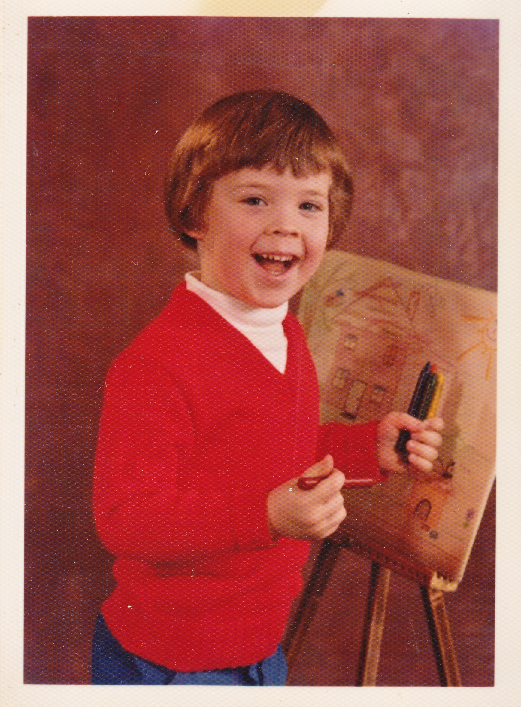 Keith MacLelland as a kid smiling at the camera with an easel and artwork behind him and crayons in his hand.