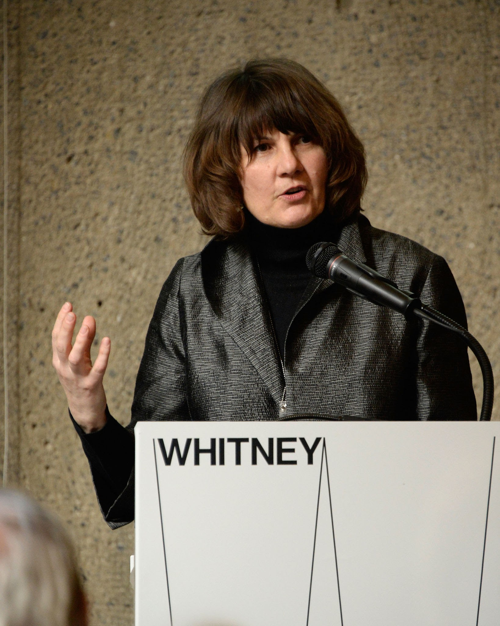 Michelle Grabner stands at a podium that says Whitney. Her arm is raised; she is in the middle of speaking. Michelle has short brown hair with bangs and wears all black.