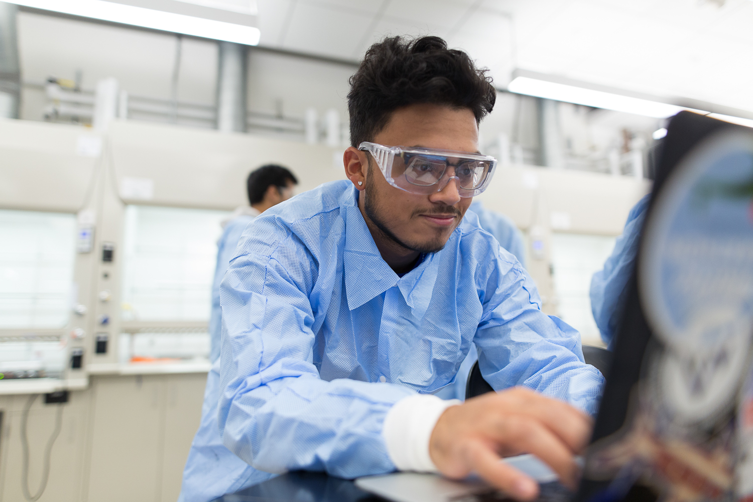 A close up of a student in the lab with protective glasses on.