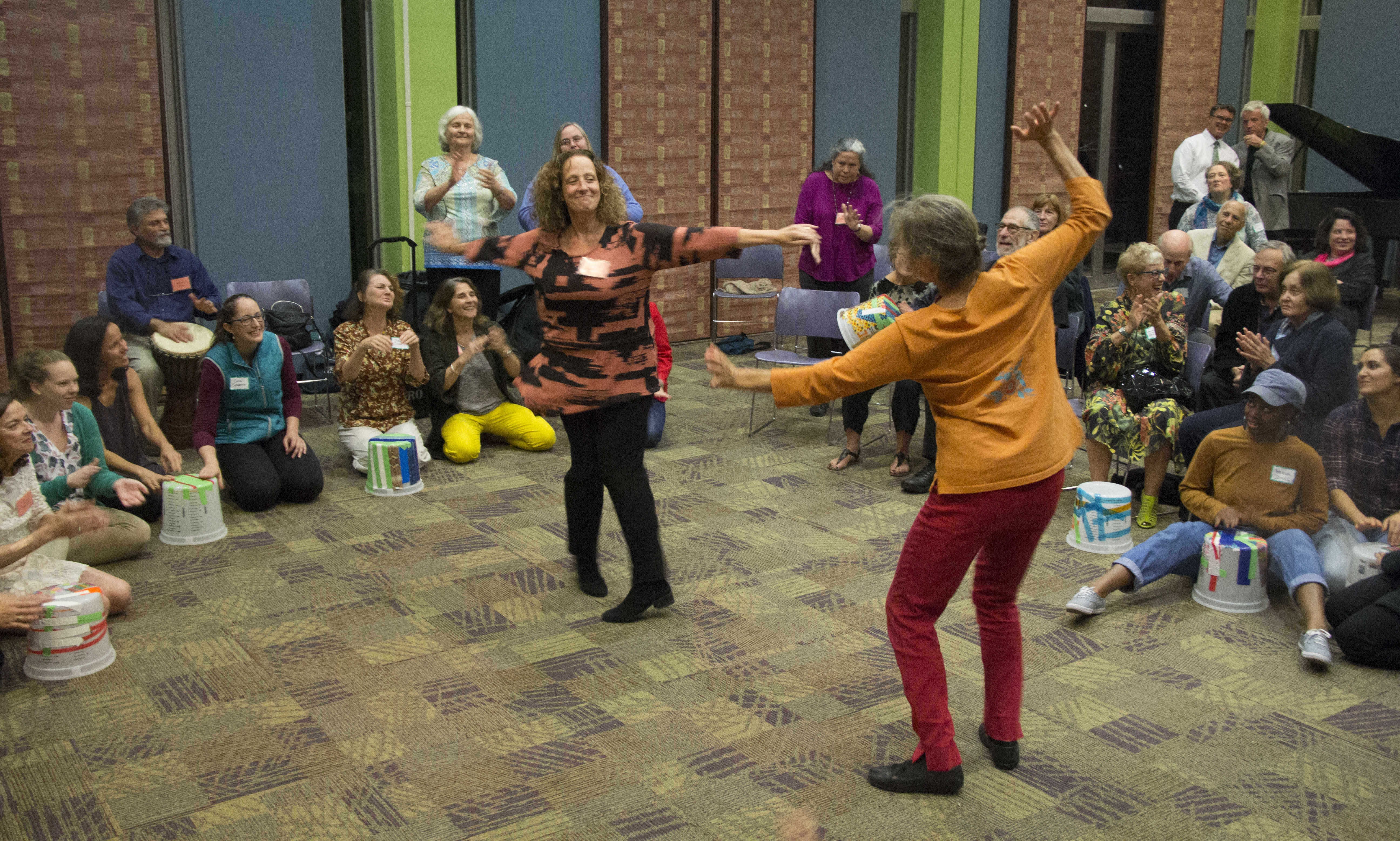 Two women dancing in the middle of a circle of people sitting down.