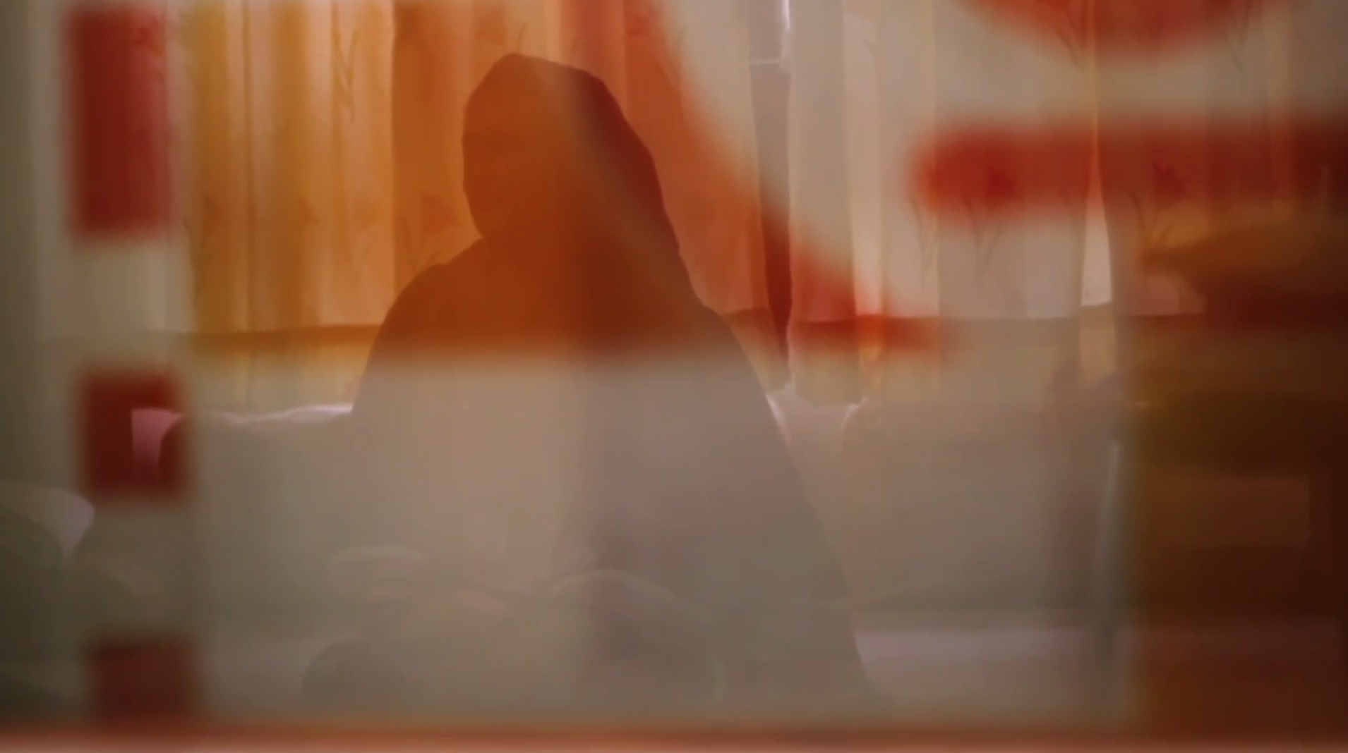 Silhouette of an unidentifable woman behidn a curtain.