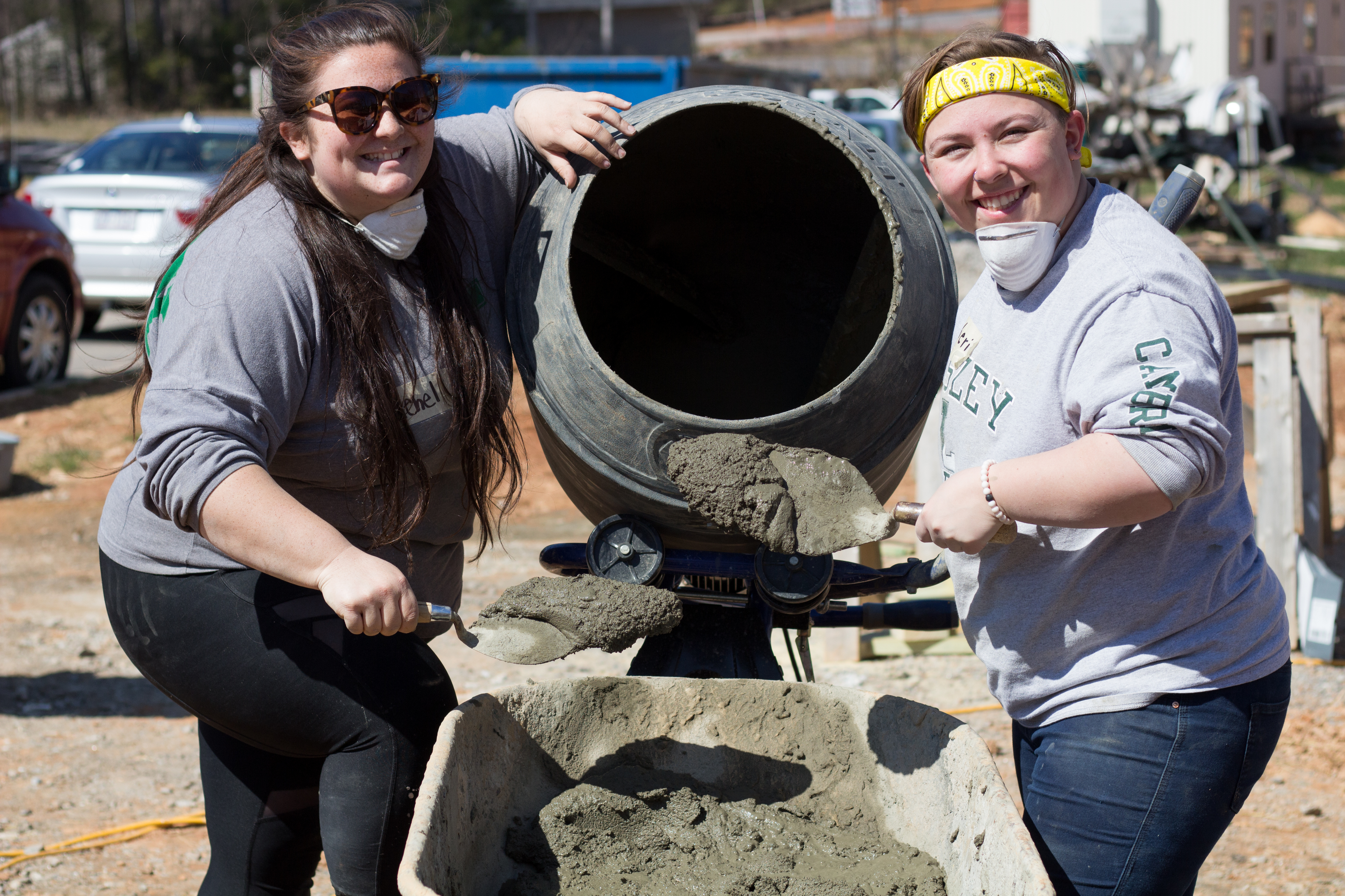 Rachel DiGangi mixing cement on Alternative Spring Break with another student.