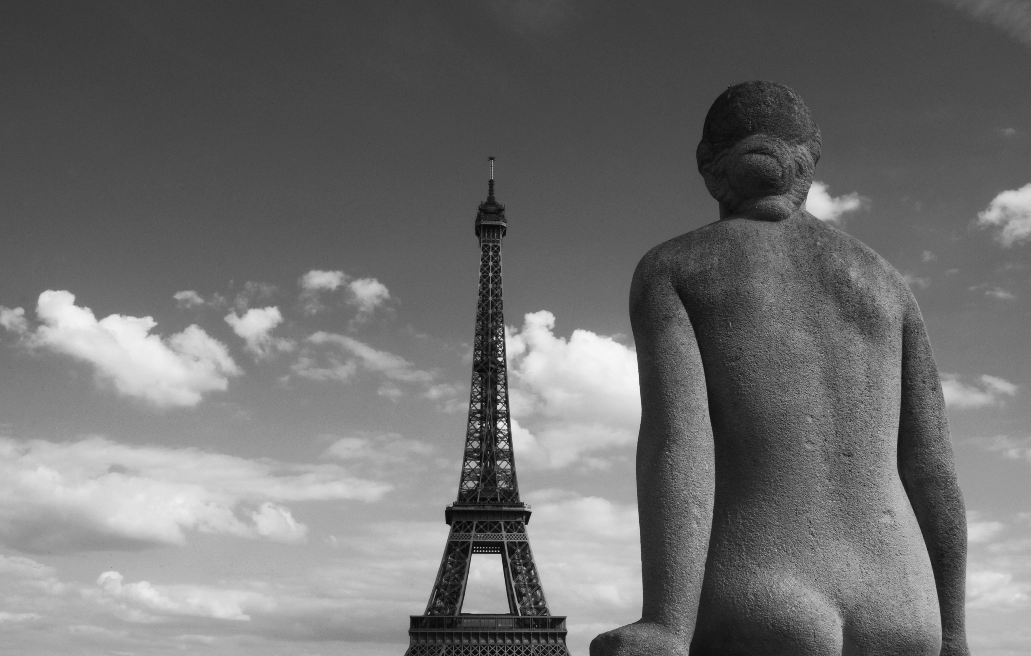 black and white photo of a woman facing the eiffal tower