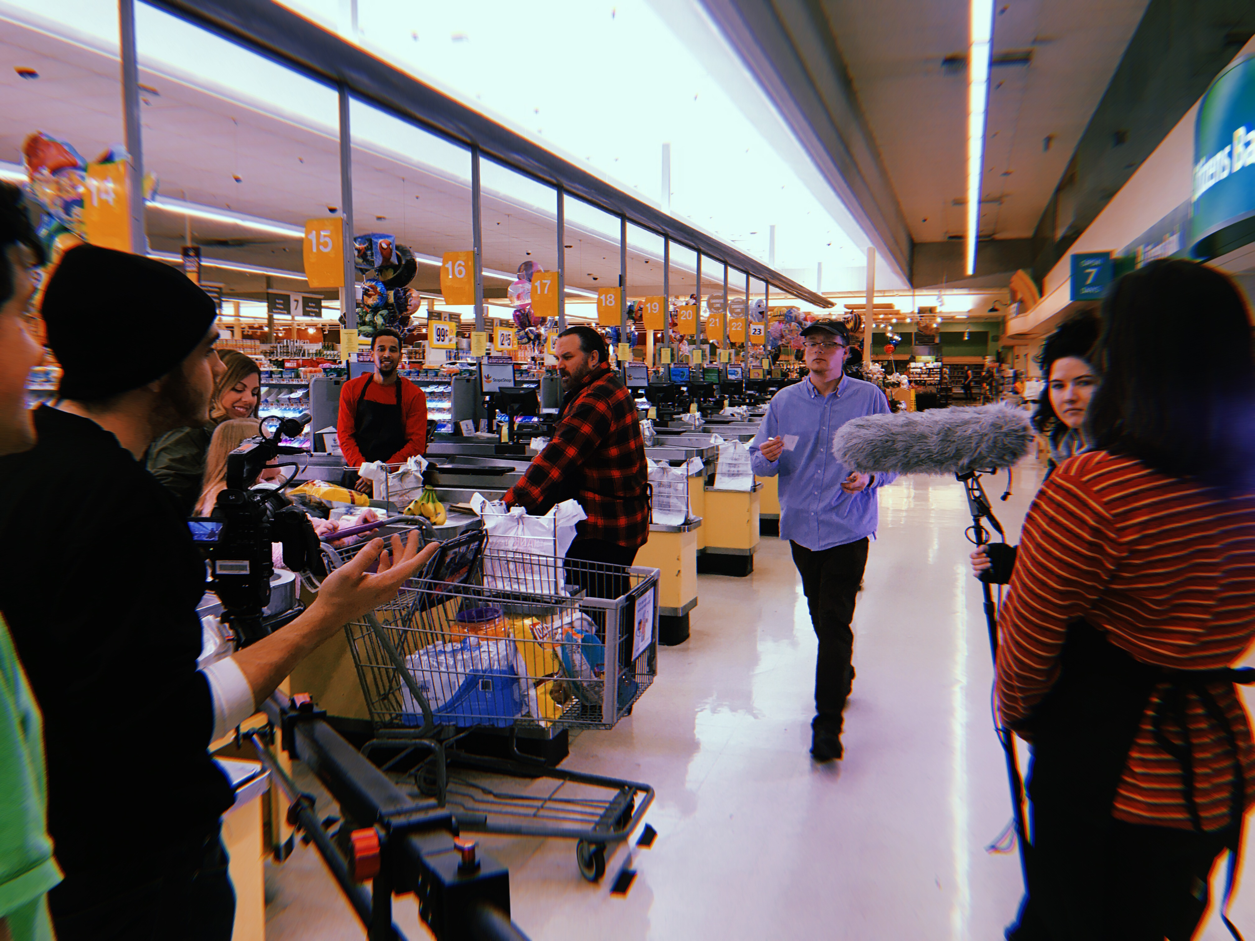 students filming a movie in a grocery store