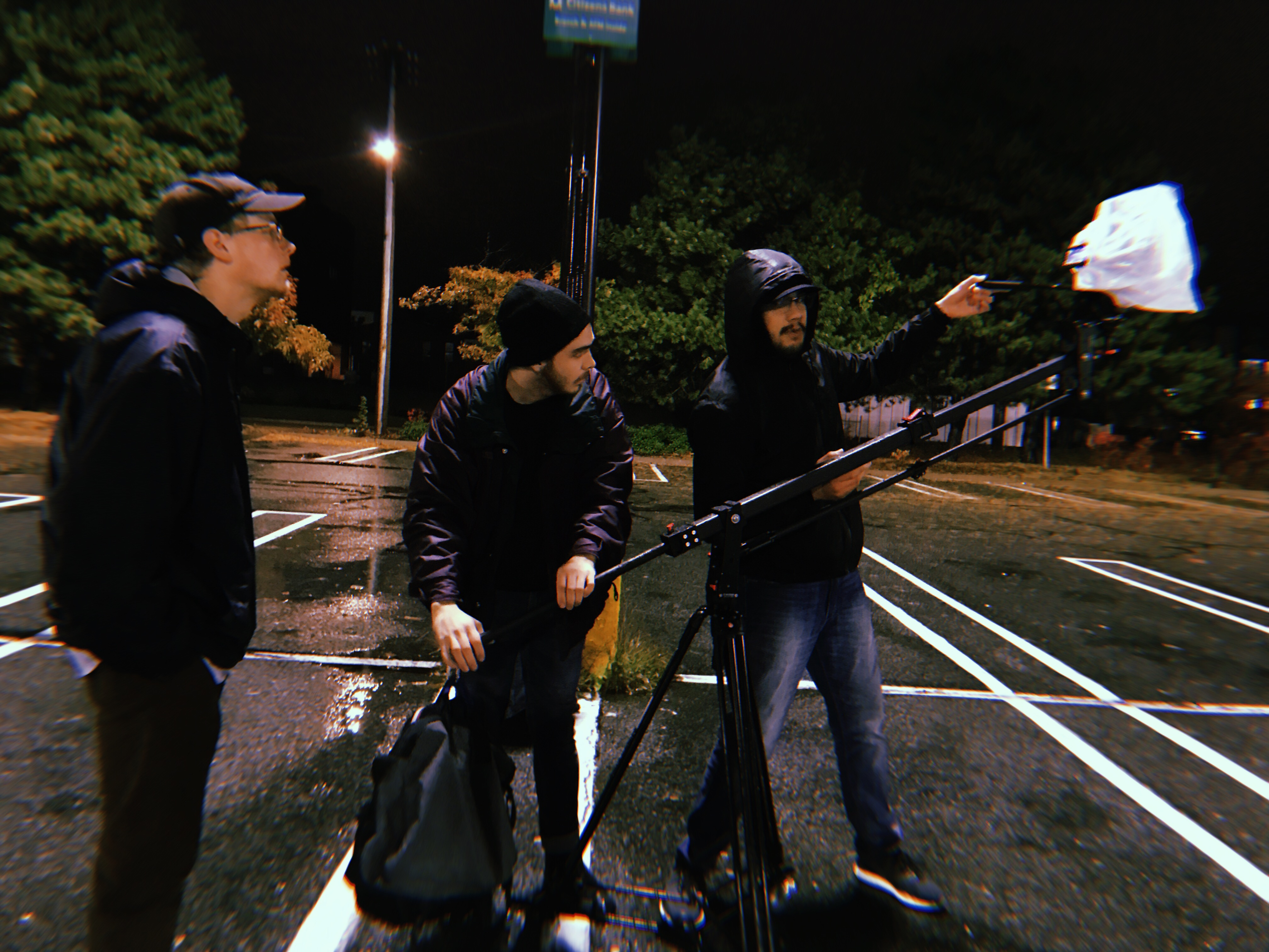 three film students set up a camera to record in an empty parking lot at night in the rain