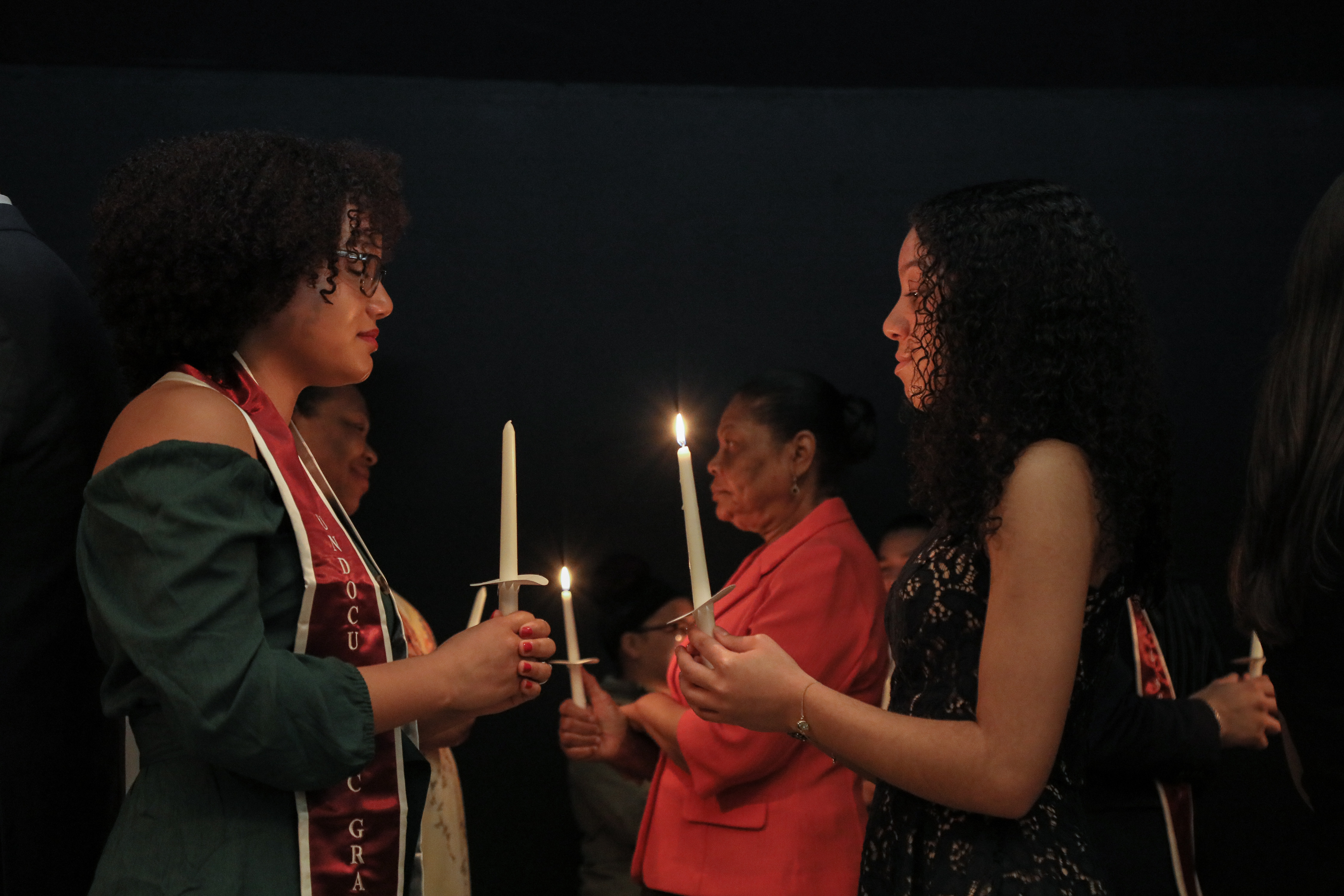 Women stand facing each other on the stage with lit candles.