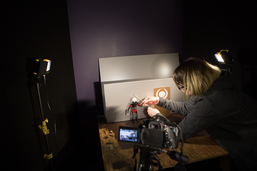 Woman manipulating small robot figure in front of a camera set-up on a tripod