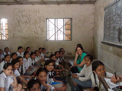 a room full of young students sitting on the floor facing the chalkboard