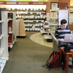 student using laptop in bookstore