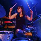 Lesley alum Caitlin Kalafus at her drum set, playing the drums on stage.