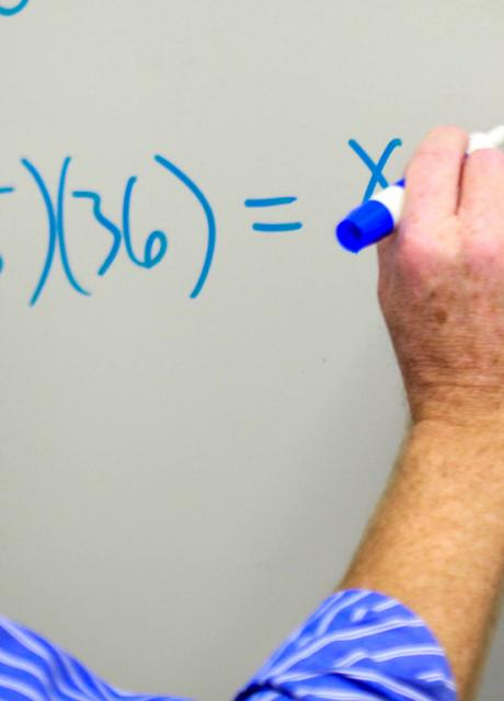 person writing formula on white board