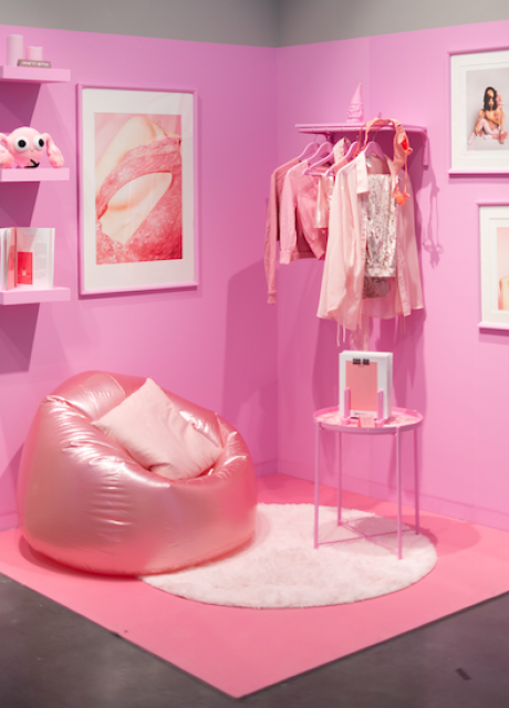 A corner of a gallery in the Lunder Arts Center painted pink with a pink beanbag, shelves and picture frames.