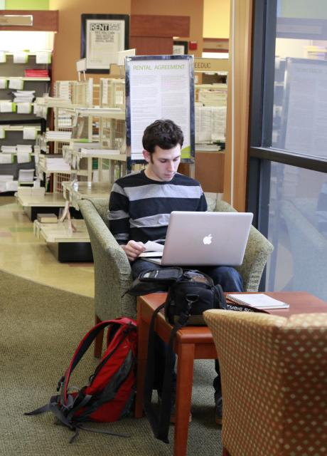 student working on laptop in lesley university bookstore