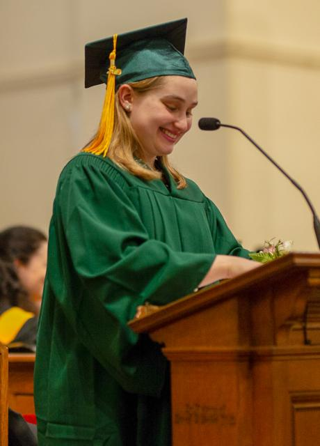 Olivia Gaffney smiles at the podium in her green graduation cap and gown