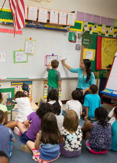 teacher teaching small children at a board