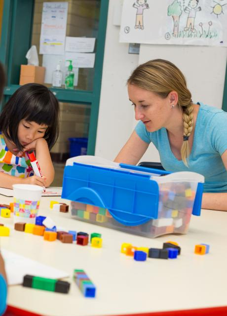 elementary teacher helping a student with blocks