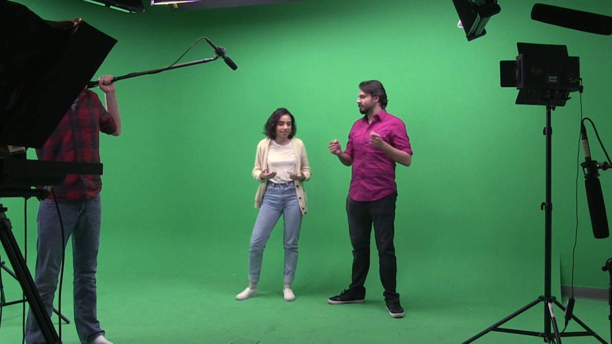 young woman explaining something to man in front of green screen