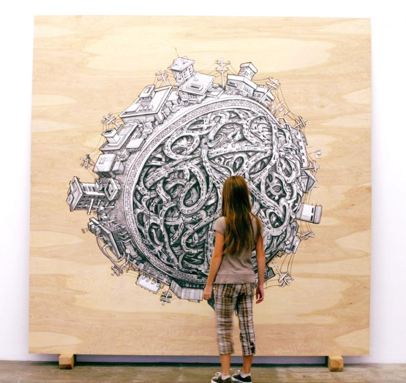 Teenage girl looking large installation work of illustration of globe and cityscapes printed on wood