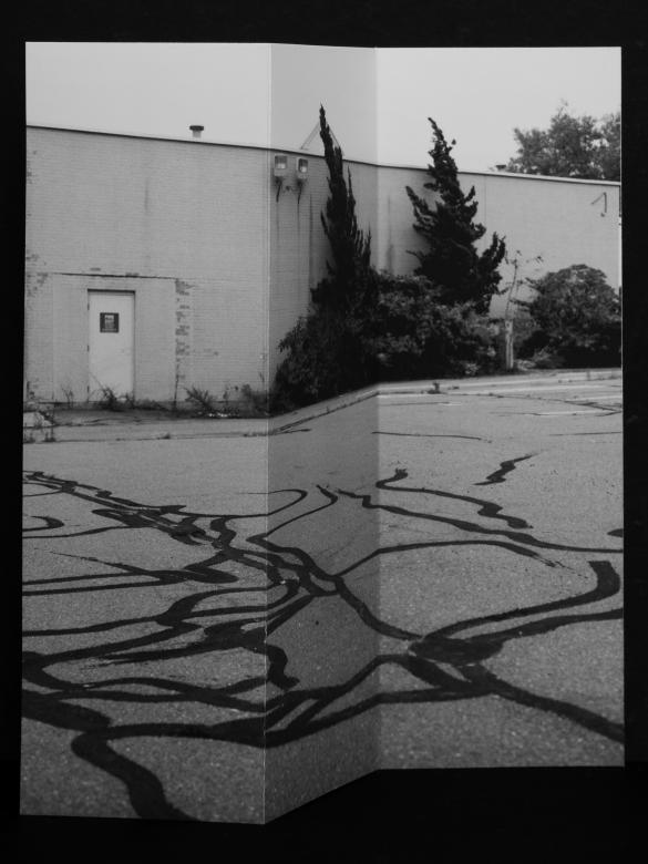 black and white photo of empty parking lot behind brick building