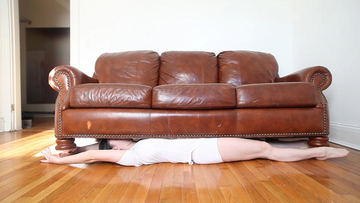 photo of woman laying underneath a red leather couch on hardwood floor