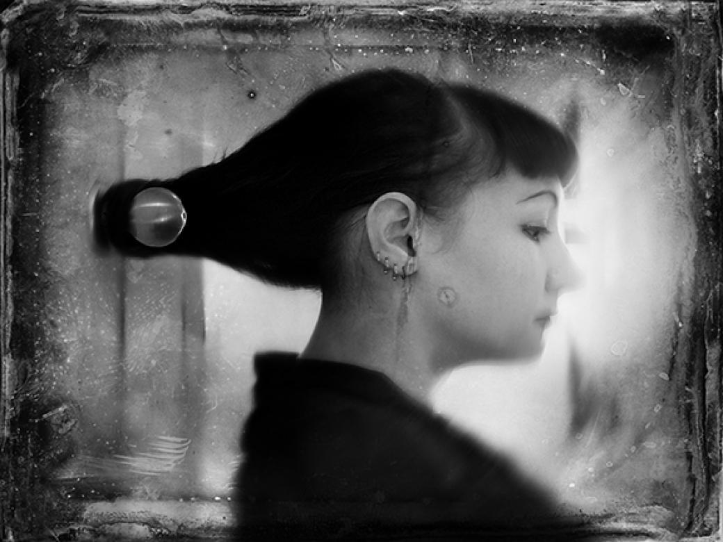 black and white image of woman's profile with hair tied around a doorknob