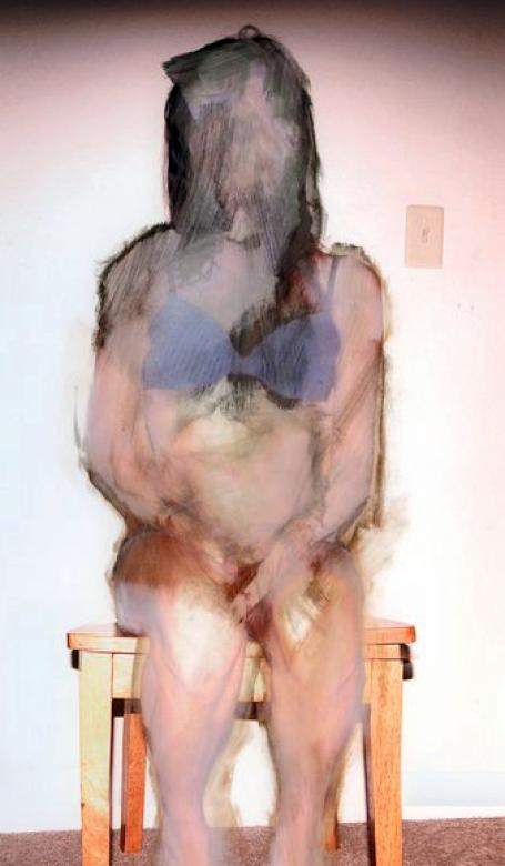 obscured photograph of woman sitting upright in chair
