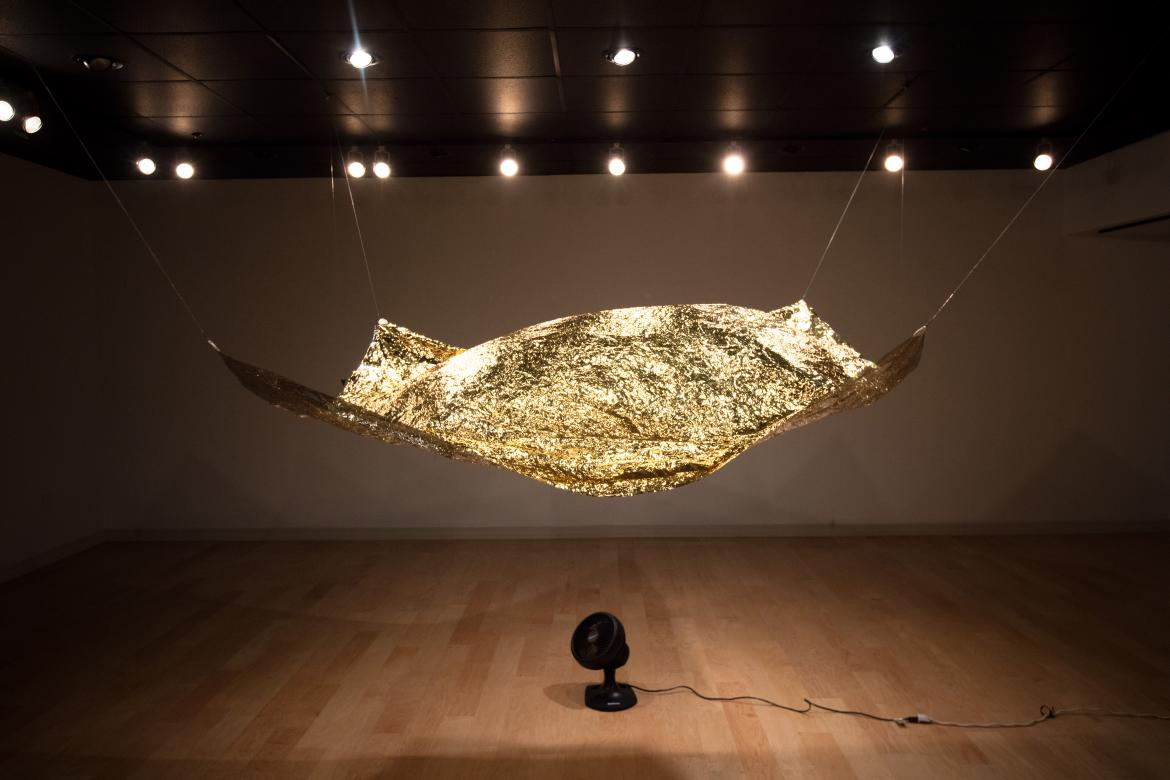 gold tarp hanging from gallery ceiling with fan below blowing it up surrounded by dim lights