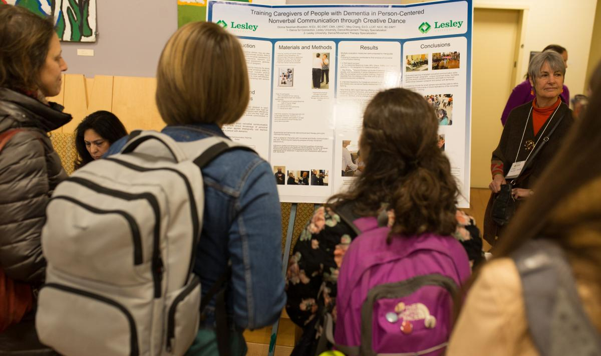Participants listen to presenter talk about her poster topic
