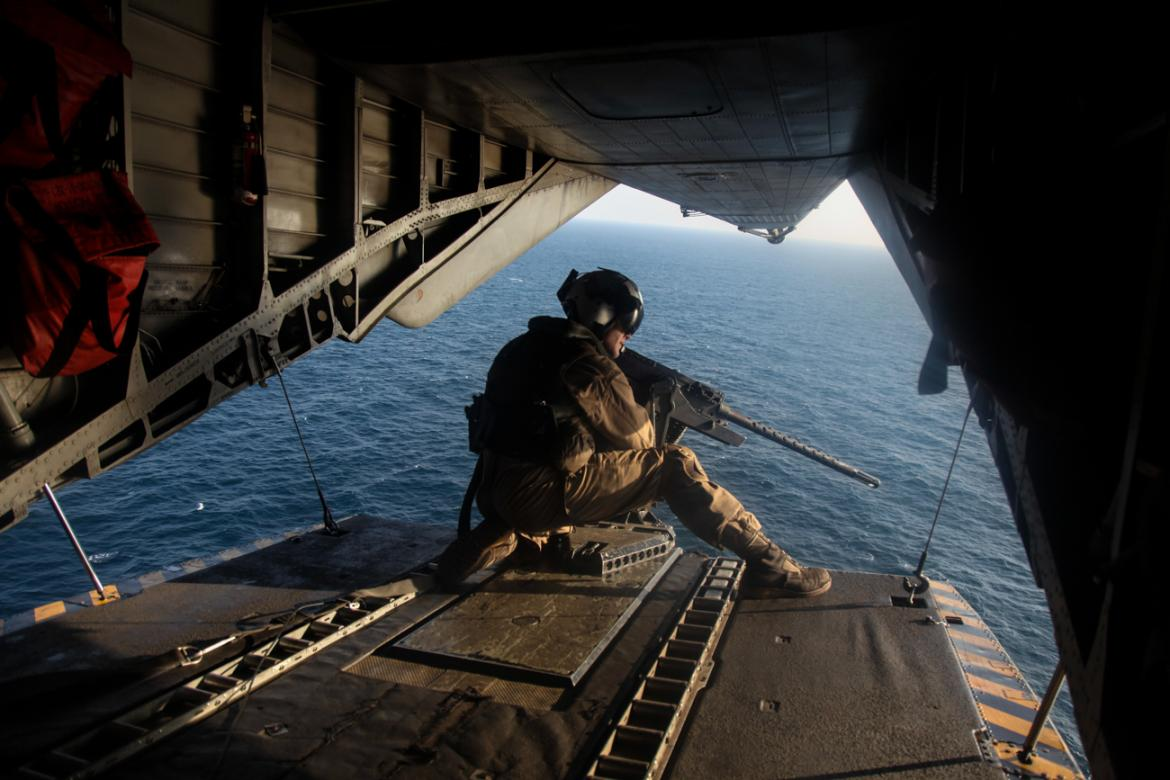 GULF OF OMAN, U.S. Marine Sgt. Gilbert Hopper provides security while flying aboard a CH-53E Super Stallion. Man crouched with gun on edge of open plane back with water in the background.