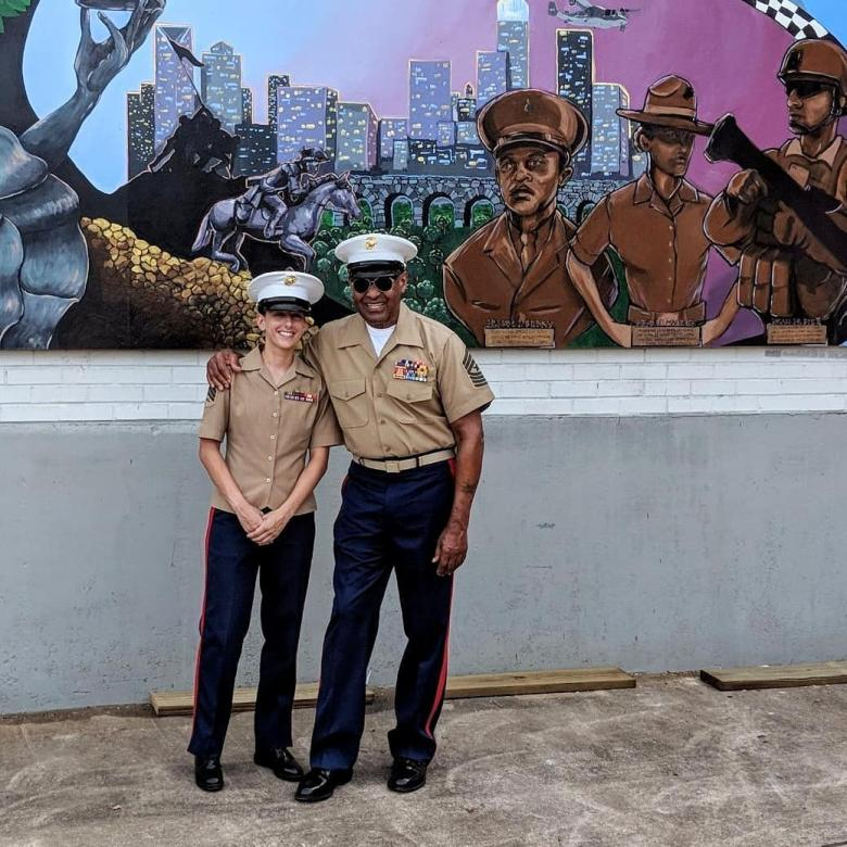 McKelvey stands with retired Sgt. Maj. John Canley in front of his image on a mural she created. He received the medal of honor two weeks later.