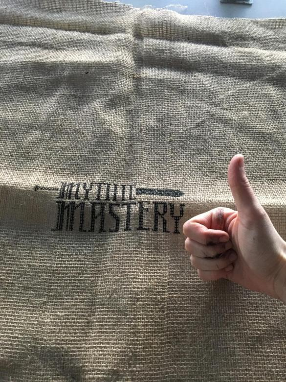 "someone makes a ""thumbs up"" on a burlap bag with black text printed on it"