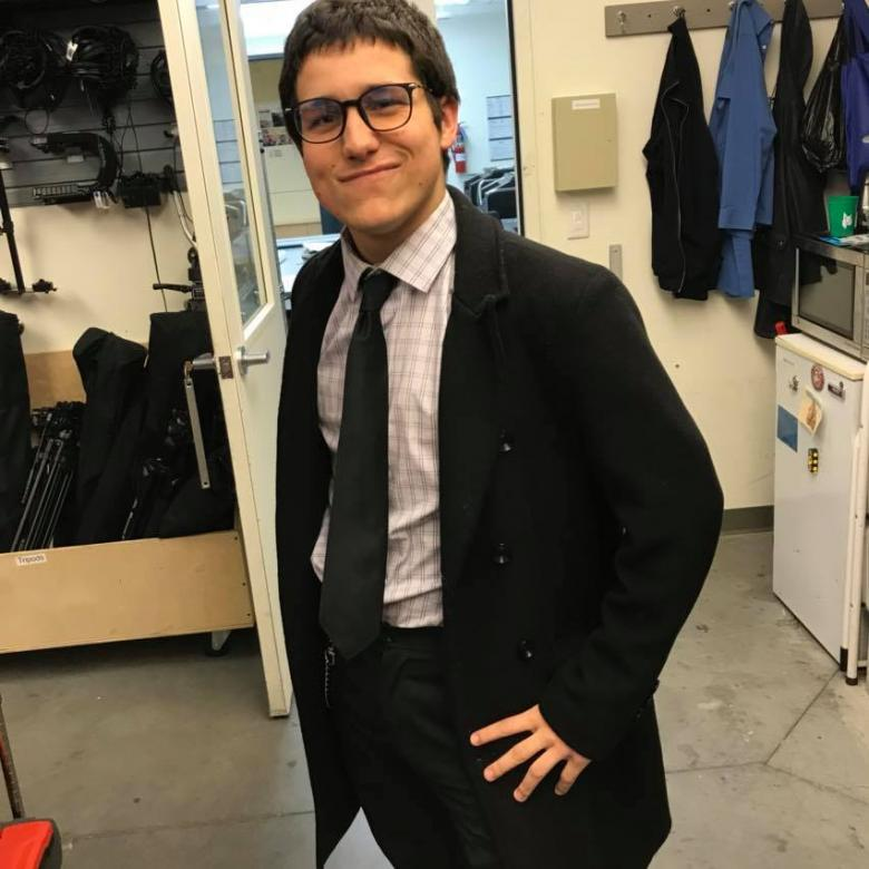 student poses in office wearing a suit and tie