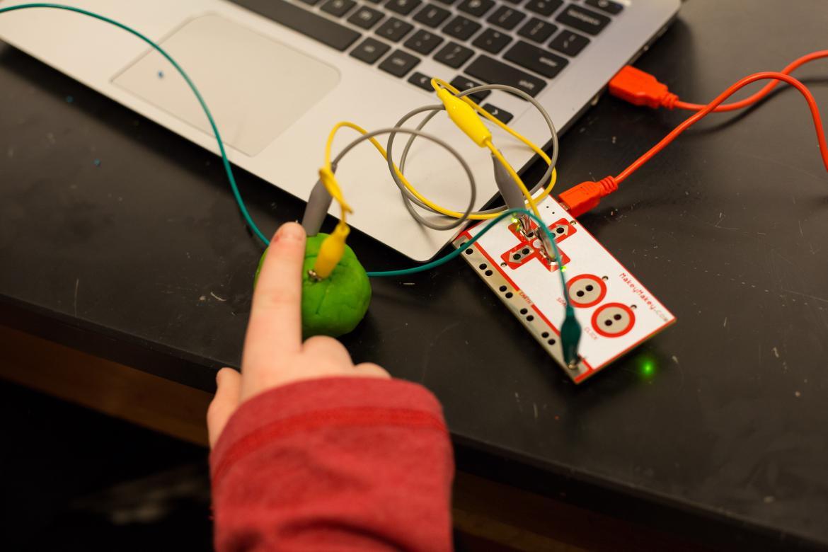 Young student completing a experimental circuit with their finger