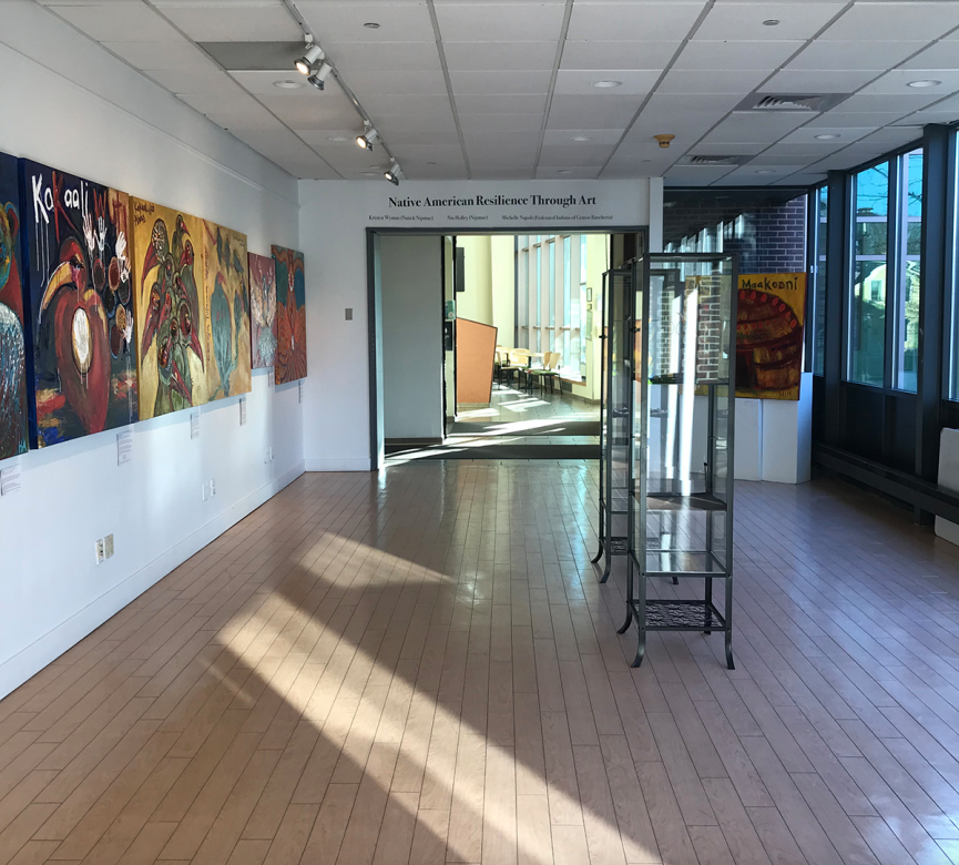 view of gallery space with sun light coming through on floor and paintings hanging on the wall
