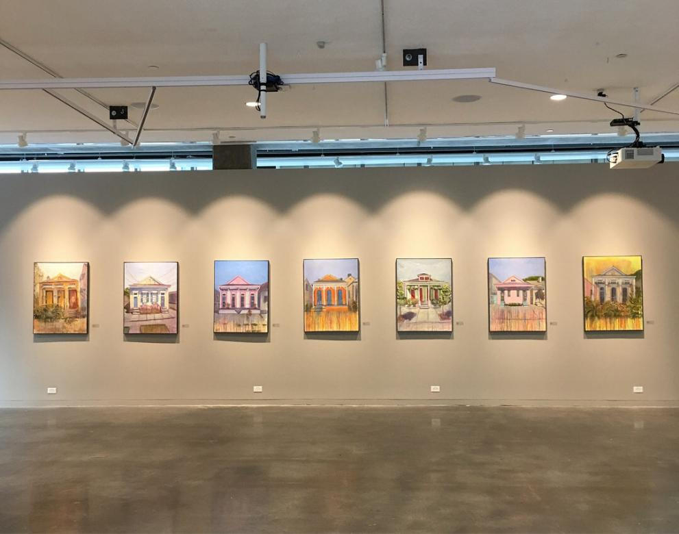 gallery photo with paintings of houses all lined up under spotlights.